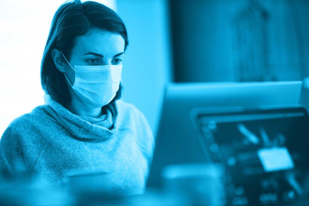 Eine Frau sitz am PC mit einem Mundnasenschutz