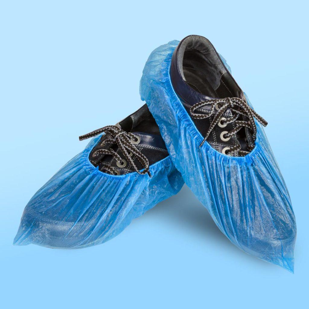 2 Schuhe, die einen medizinischen Überzieher tragen