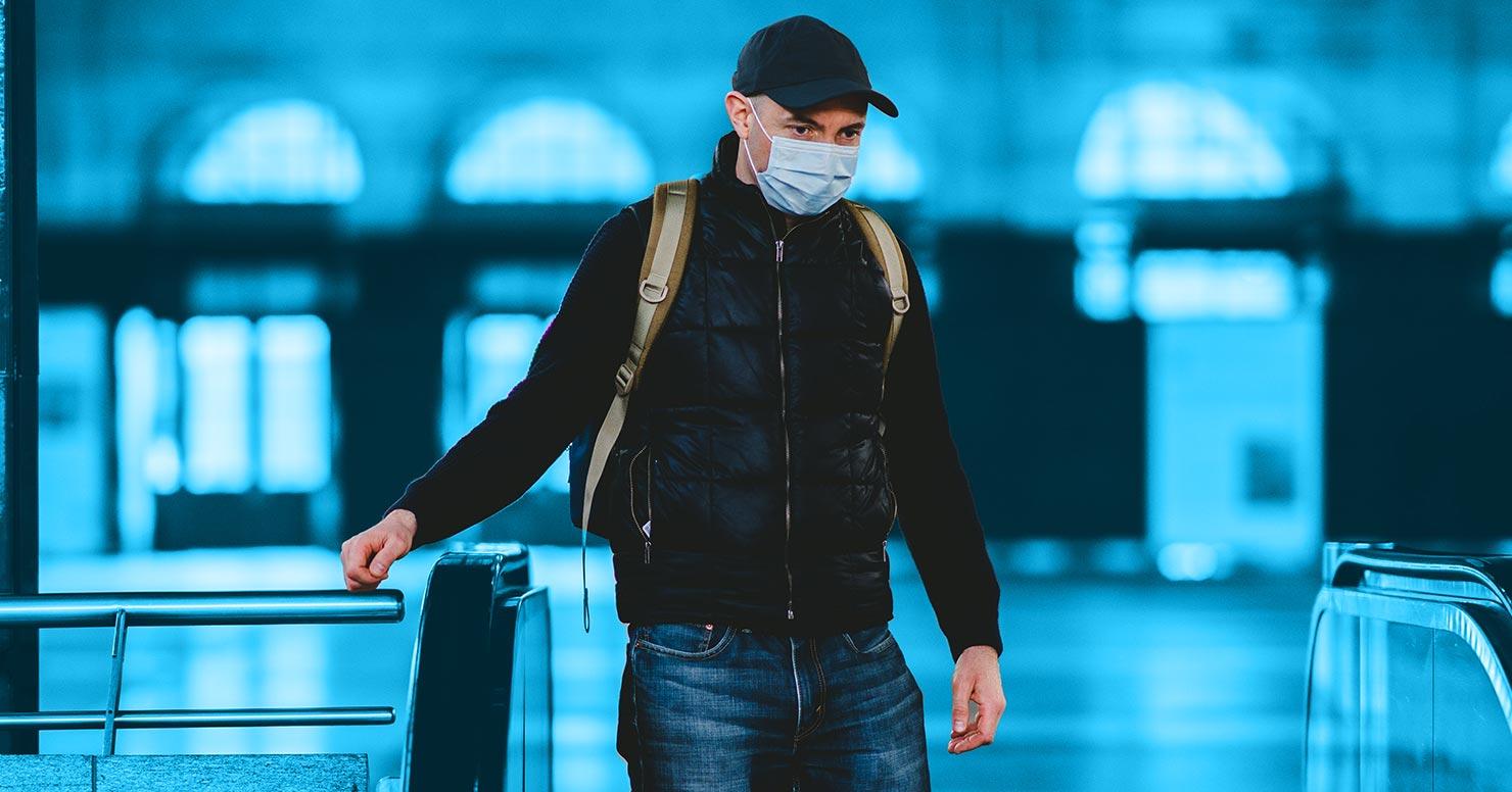 Mann mit Mundnasenschutz steht am Eingang zu einer U-Bahn-Station